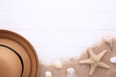 Beach hat with seashells on white wooden table royalty free stock photos