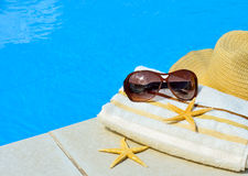 Beach hat, sunglasses, bath towel, starfish near the swimming po Royalty Free Stock Photo