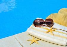 Beach hat, sunglasses, bath towel, starfish near the swimming po Royalty Free Stock Photo