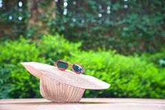 Beach hat with sunglasses. With green nature background. Summer holiday or vacation concept royalty free stock image