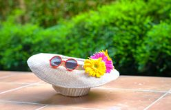 Beach hat with sunglasses and gerbera daisy flowers. With green nature background. Summer holiday or vacation concept royalty free stock photos