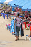 Beach Hawker. A local hawker walks along the beach trying to sell her goods to the tourists stock photo