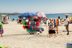 Beach hawker with stacked hats, balls and scarves royalty free stock photos
