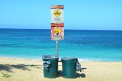 Beach hazard signs and dustbins. Beach hazard signs warning of strong currents and high waves with two dustbins on the edge of a turquoise blue tropical Stock Photography
