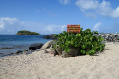 Beach Hazard Warning Sign. A beach hazard warning sign for coral and sea urchins on a tropical island stock photo