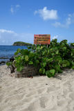 Beach Hazard Warning Sign. A beach hazard warning sign for coral and sea urchins on a tropical island stock images