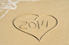 2014 on the beach. A heart drawn on the sand of a beach with the number 2014, as the new year, written inside stock photos