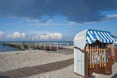 Beach in Heiligenhafen. Beach with canopied wicker beach chairs and the old pier in Heiligenhafen at the Baltic Sea Stock Image
