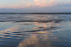 The beach at high tide at sunset with reflection of clouds Royalty Free Stock Photo