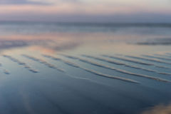 The beach at high tide at sunset with reflection of clouds Royalty Free Stock Photography