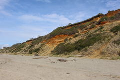 Beach hillside with red rock. Stock Images
