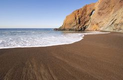 Beach and Hole. Dark sand and a rock formation on the California coast Royalty Free Stock Photography