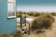 Beach Holiday. A view of a blue painted wooden beach hut with wooden terrace, looking towards the beach. An upturned white boat to front of beach hut rests Stock Images
