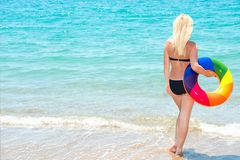 A beach holiday.Beautiful woman in bikini with inflatable circle looks out to sea. stock photos