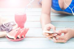 Beach holiday concept with watermelon and cocktail, woman in bik. Ini relaxing by smartphone Royalty Free Stock Photos