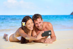 Beach holiday couple taking selfie with smartphone. Lying down relaxing and having fun holding smart phone camera. Young beautiful multicultural Asian Caucasian Royalty Free Stock Image