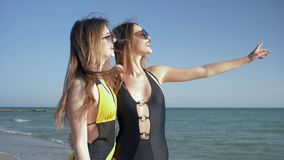 Beach holiday, girlfriends in swimsuit and sunglasses look into distance and laugh. At quay stock video