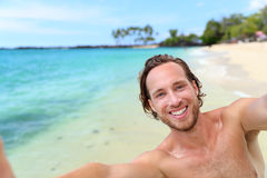 Beach holiday man taking selfie on travel vacation. Handsome young guy smiling at camera for self-portrait picture with smartphone on summer getaway. Happy royalty free stock photo