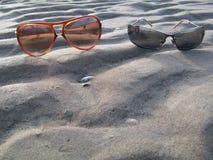 Beach holiday. Two sunglasses sunbathing on the beach Royalty Free Stock Photos
