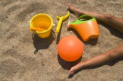Beach holidays. Various colorful beach toys for children and two tanned legs lying in the sand on a sunny day Stock Photography