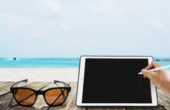 The beach holidays, Hand writing on digital tablet with sunglasses, on wooden terrace at tropical beach. copy space on screen. The beach holidays, Hand writing Stock Image