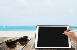The beach holidays, Hand writing on digital tablet with sunglasses, on wooden terrace at tropical beach. copy space on screen. The beach holidays, Hand writing Stock Photo