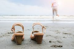 Beach holidays travel vacation lifestyle concept. Happy middle aged business woman take off shoe run into the sea with barefoot enjoying beautiful beach Stock Image