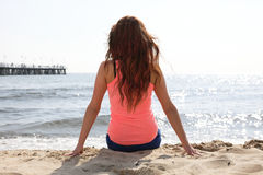 Beach holidays woman enjoying summer sun sitting Stock Photography