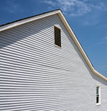 Beach house. An abstract of a beach house with white wood siding against a blue sky filled with whispy clouds Royalty Free Stock Photos
