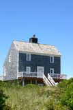 Beach house. Charming beach house with grey cedar shake siding against blue sky royalty free stock images