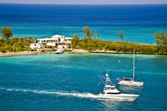 Beach House. Beautiful white house on a peninsula in the Bahamas with boats passing by Royalty Free Stock Photography