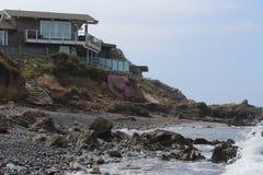 Beach House on Rocky Coastline. Beach house built on cliffs on rocky coastline at Cambria, CA Stock Photography