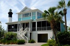 Beach house near light house Royalty Free Stock Photography
