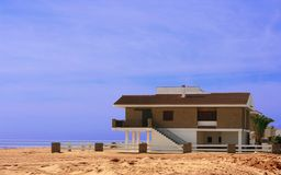 Beach house sitting on the sand. Single brick beach house sitting completely on the sand. It has a sand patio surrounded by a white wood fence and a green palm Stock Photo
