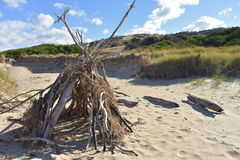 The Beach House. A small tipee built out of drift wood on the beach Stock Image