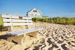 Beach house sunrise. Bench at the end of the boardwalk across the dunes is bathed in early morning light stock image