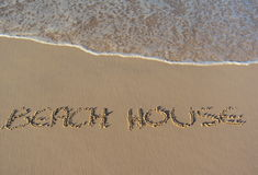 Beach house written in the sand Stock Images
