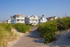 Beach Houses. Along the New Jersey shore,  with a path through the sand dunes in the foreground and a blue sky background Royalty Free Stock Photos