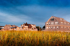 Beach houses behind dunes. Maine beach houses in morning summer sun Royalty Free Stock Images