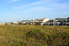 Beach houses. Row of beach houses on the grass covered sand dunes; Sunset Beach, North Carolina royalty free stock photography