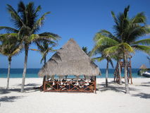 Beach Hut. A grass-roofed hut on a white sandy beach in Mexico is right in between some palm trees Stock Photos
