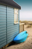 Beach Hut. View of the side of a wooden beach hut with a blue surf board. View looking towards the beach. Located in Christchurch, Dorset Hampshire UK Royalty Free Stock Photography