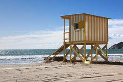 Beach hut. View of a yellow and white beach hut on a sunny day Stock Image