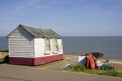 Beach Hut. Old red and white beach hut with sea in the background and old boat royalty free stock image