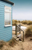 Beach Hut and Boat. View of the side of a blue wooden beach hut with wooden terrace, looking towards the coast/beach. A white upturned boat rests in front of the Royalty Free Stock Images