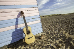 Beach hut guitar. Parlour-sized classical acoustic guitar resting against a beach hut painted in pastel pink and blue. Symbolic of vacation and beach fun Royalty Free Stock Photo