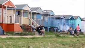 Beach hut picnic bbq. Video footage of holidaymakers enjoying beach hut picnic and bbq on the whitstable coast of kent stock footage