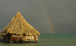 Beach hut & rainbow post storm royalty free stock image
