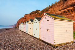 Beach hut row in pastel colors, red rock cliff background stock photos