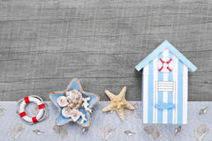 Beach hut and seashells on a grey wooden background for travel c Stock Photo